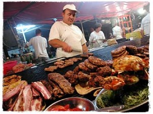 At one of the stands at the festival, a cook prepares sausages and pljeskavicas