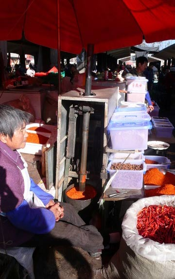 Dried chile pods and a grinder in the market.