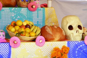 A traditional day of the dead altar with fruit, bread, and a sugar skull