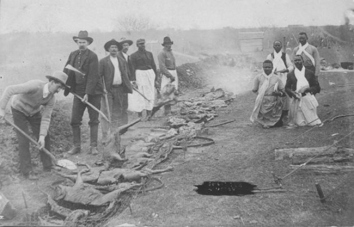Texas Men with an open-pit barbecue
