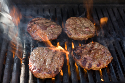 burgers smoking on a grill