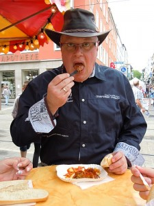 """German """"cowboy"""" enjoys a bite of currywurst at a festival in Kassel."""