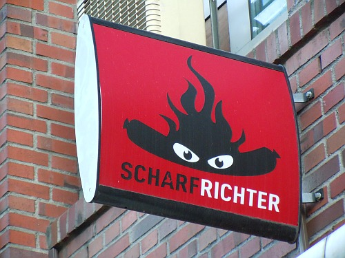Scharfrichter logo in Bremen: a sausage with a devilish flaming hot-spicy sauce